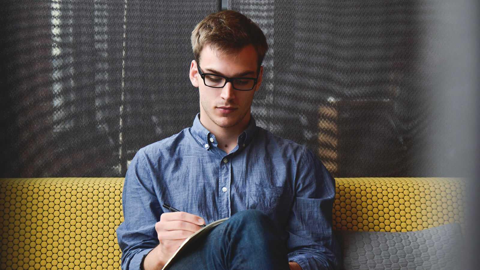 Mand der sidder og manuelt skriver data ned på hans booklet
