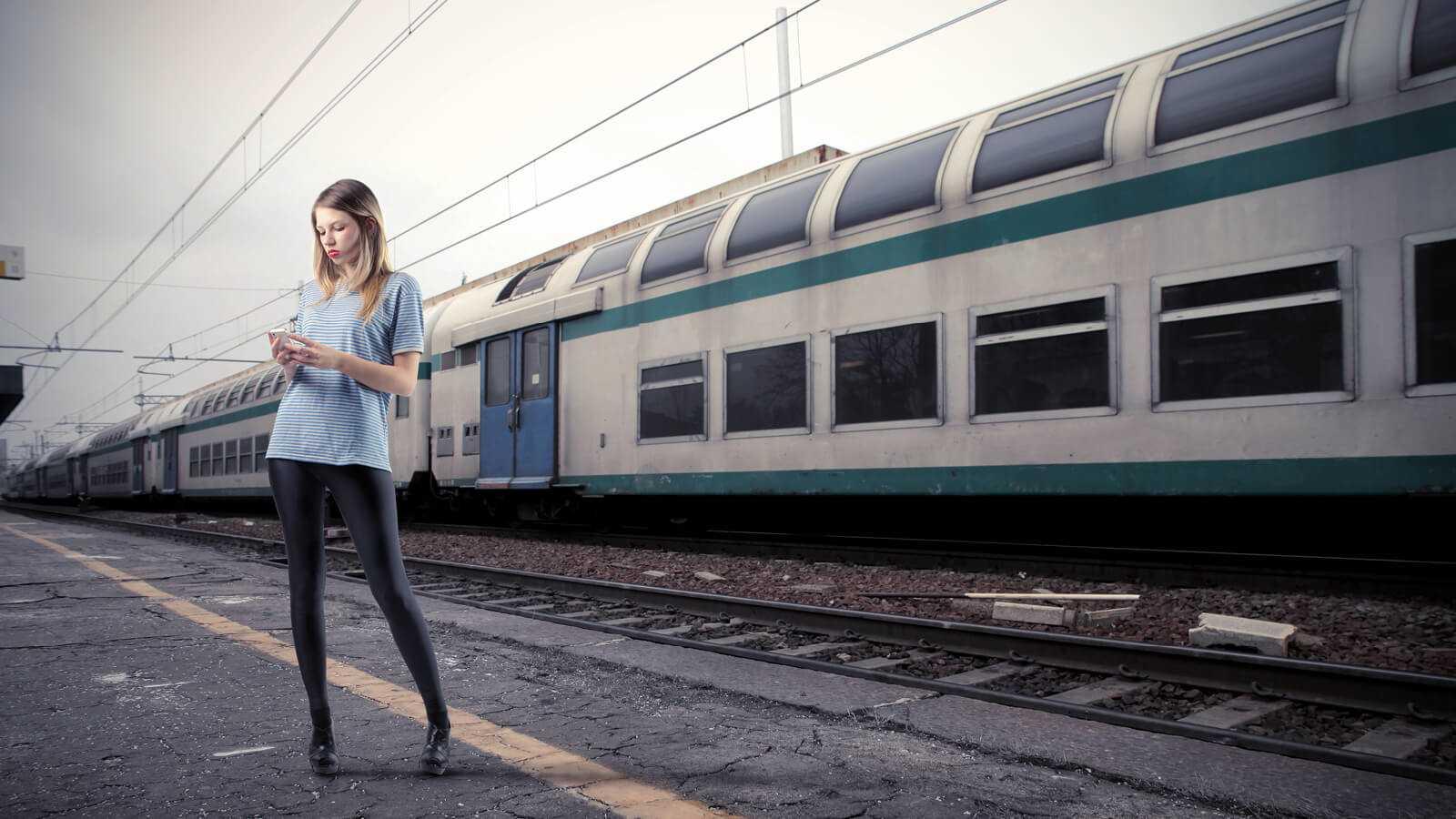 Kvinde der læser op på ADFS imens hun venter på toget.