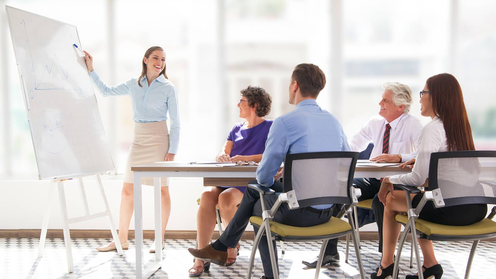 Kvinden fortæller sine kollegaer hvor mange fordele man kan få ved at bruge Pronestor