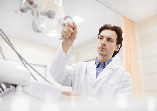 En tandlæge der er ved at rette deres lys på hans patients tænder