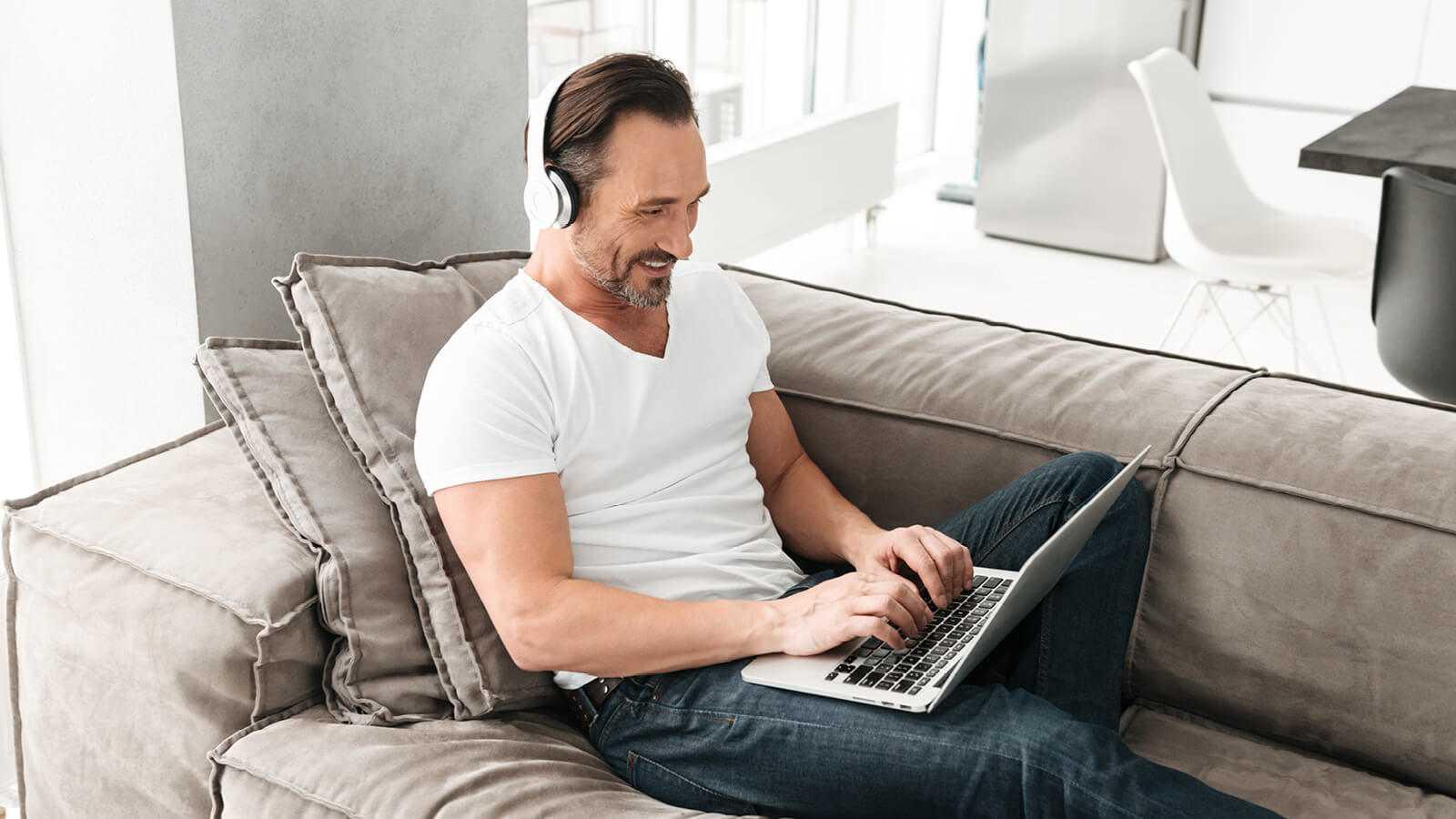 En mand der sidder hjemme i hans sofa og arbejder