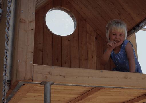 En pige der sidder i et legehus der er bygget af Elverdal