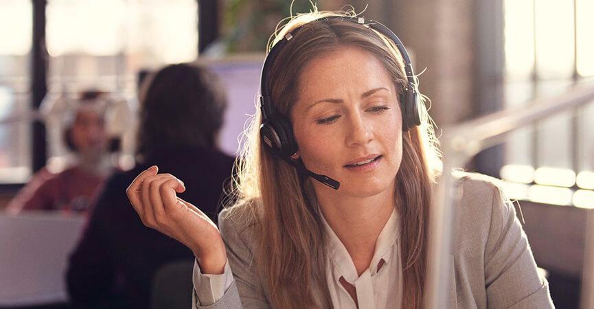 Kvindelig receptionist der snakker med en kunde igennem hendes Impact headset fra EPOS   SENNHEISER