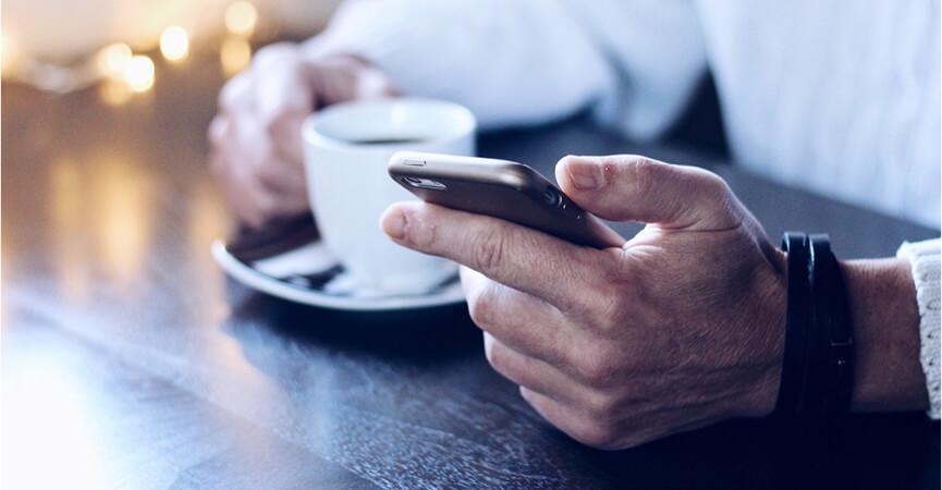 En mand der sidder og læser firma mails på hans telefon på en kaffebar