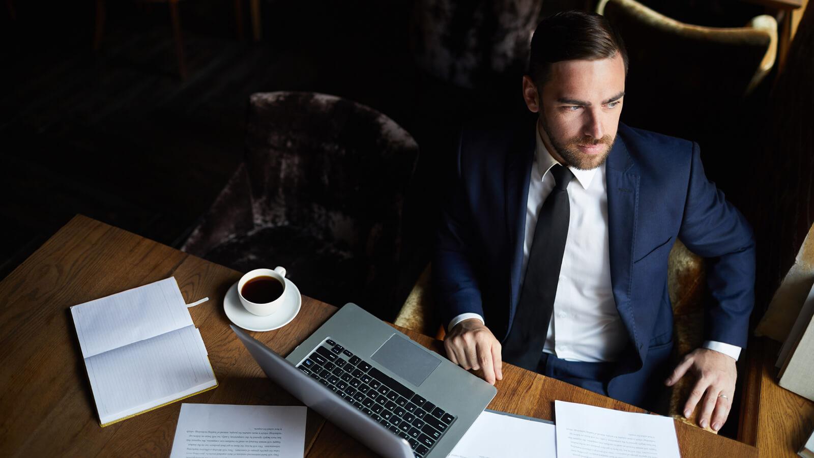 En mand der sidder og på hans kontor, han kigger ud af vinduet fordi han ikke har nogle bekymring omkring sikkerhed, da han har en effektiv Firewall