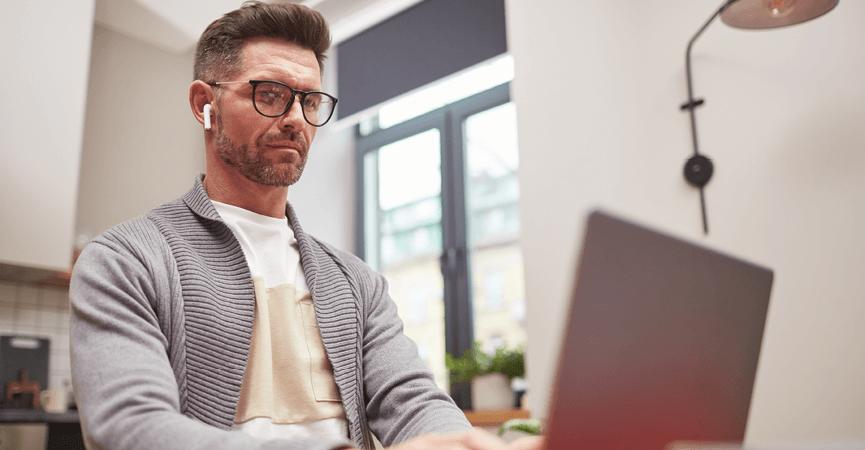En mand der sidder derhjemme og arbejder på hans PC uden bekymringer om hackere og andre cybercrime, fordi hans firma har købt firewalls til alle deres medarbejdere.